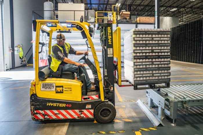 man in forklift moving pallets in a warehouse
