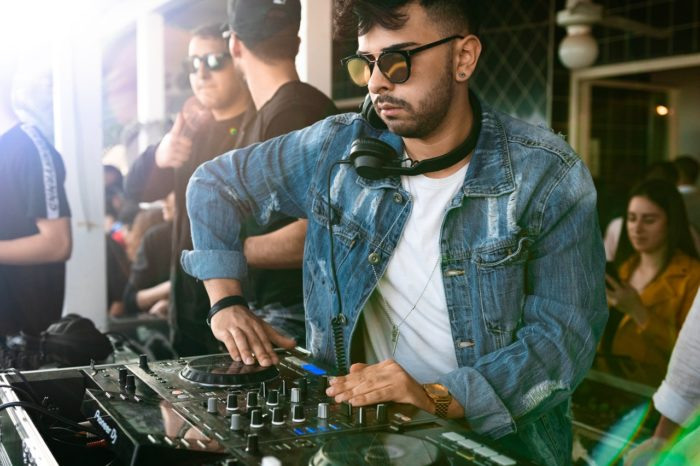 DJ in a jean jacket playing an outdoor party