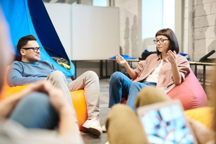 Man and a Woman Discussing Information, Sitting on Beanbag Chairs