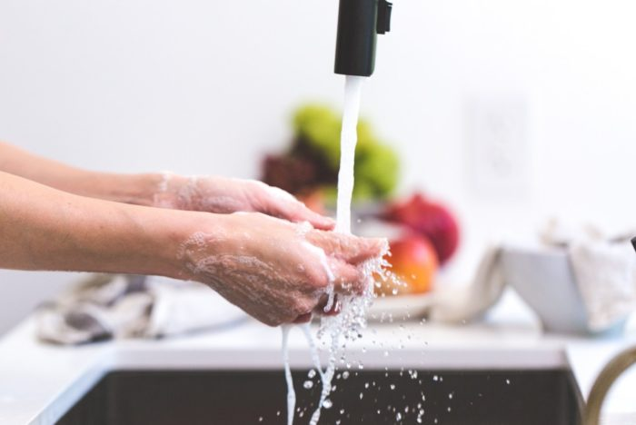 Person Washing Hands Over the Sink, With Soap